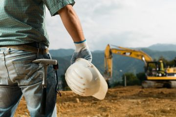 closeup back view of male engineer standing on construction site holding white hardhat