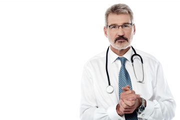 Mature male physician with stethoscope over white